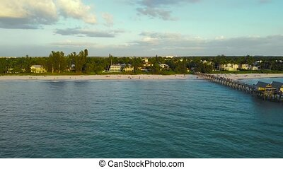 Coast and the beach near the pier leaving into the ocean. Drone flies forward from the ocean to shore along a large wooden fishing pier. People walk along the ocean. Luxury houses near the ocean.
