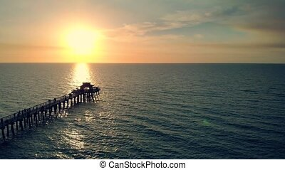 Drone aerial of Naples coastline into the Naples fishing pier with the sunset in the background. Sunset over horizon and wooden pier of caribbean beach of Naples in Florida. Drone is flying forward.