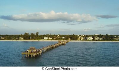 Naples Beach and Fishing Pier at Sunset, Florida. Drone flies around a fishing pier in Naples, Florida USA. Naples, Florida is a tourist town in the USA. Drone flying around the orbit, aerial view.