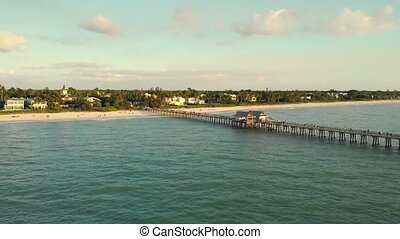 Naples Beach and Fishing Pier at Sunset, Florida. Drone flies back. Drone flies back, flying away from pier. Drone aerial of Naples coastline into Naples fishing pier with the sunset in the background