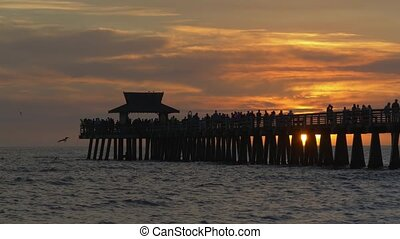 People walk along pier at sunset time. Sun sets in the ocean against backdrop of a pier in Naples, Florida. Naples Beach and Fishing Pier at Sunset. Dark silhouette of a pier over the water at sunset.