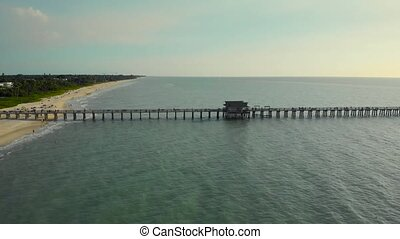 Naples Beach and Fishing Pier at Sunset, Florida. Pier in Calm Ocean with High Rises in the Distance. Flying along a wooden long pier at sunset time. Drone flying from left to right.