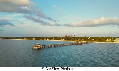 Pier in Naples by Aerial Drone. Drone flies around a fishing pier in Naples, Florida USA. Sunset over horizon and wooden pier of caribbean beach of Naples in Florida. Golden sunset with fishing pier.