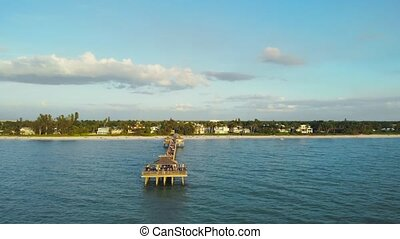 Pier in Naples by Aerial Drone. Drone flies around a fishing pier in Naples, Florida USA. Coast and the beach near the pier leaving into the ocean. Drone flying around the orbit. Naples Beach Pier.