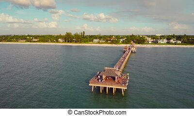 Naples Beach and Fishing Pier at Sunset, Florida. Sunset over the Gulf of Mexico, Drone flying above pier. People walk on a pier in Naples, Florida to watch the sunset.