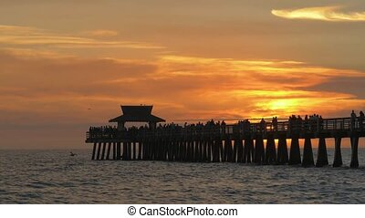 People walk along pier at sunset time. The sun sets in the ocean against the backdrop of a pier in Naples, Florida. Sunset over horizon and wooden pier of Naples in Florida. Dramatic sky during sunset