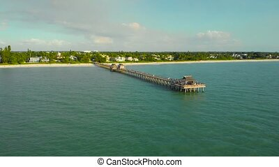 Drone flies around a fishing pier in Naples, Florida USA. Drone flies back, flying away from the pier. The coast and the beach near the pier leaving into the ocean. Beach near the ocean pier, aerial.