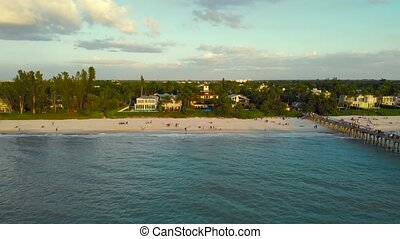 Naples Beach and Fishing Pier at Sunset, Florida. Naples, Florida is a tourist town in the USA. Drone flies forward from the ocean to the coast. People walk along the ocean, aerial view.