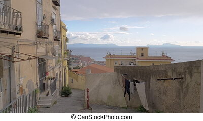 Naples view with sea, Italy. Empty street with aged houses, shabby walls, paved path and linen hanging outside