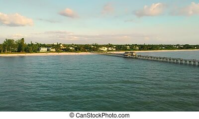 Drone flies back, flying away from the pier. Pier in Naples by Aerial Drone. Water and waves sea landscape scenery country scene background on sunny day dawning daybreak daylight sunset.