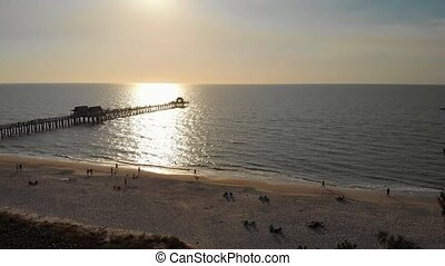Coast and the beach near the pier leaving into the ocean. Naples Beach Pier 4k aerial drone footage. Drone aerial of Naples coastline into the Naples fishing pier with the sunset in the background.