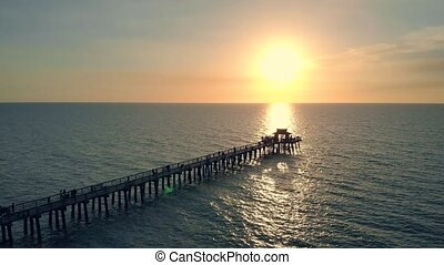 Drone flies near a pier in Naples, Florida at sunset time, aerial view. Dark silhouette of a pier over the water at sunset. Camera flies over the pier running into the ocean. Lens flare. Aerial view.