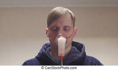 Napping man treatment oxygen mask closeup portrait unshaven messy male in dark blue bathrobe interior look into camera