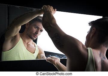 Narcissistic young man admiring his reflection - ...
