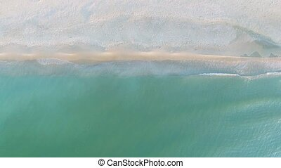 Narrow beach line, waves and ocean. Aerial view.