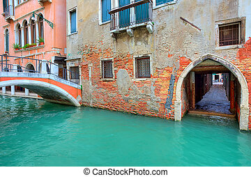 Narrow canal along old brick houses. Venice, Italy.