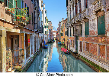 Narrow canal among ancient houses. Venice, Italy.