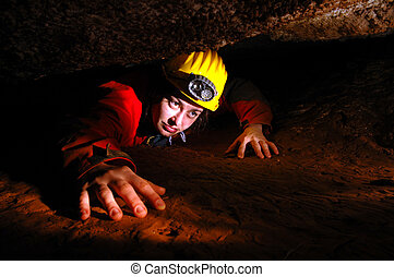 Narrow cave passage with a cave explorer