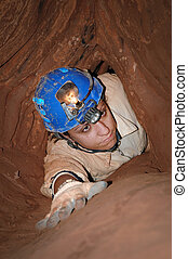 Narrow cave passage with a caver