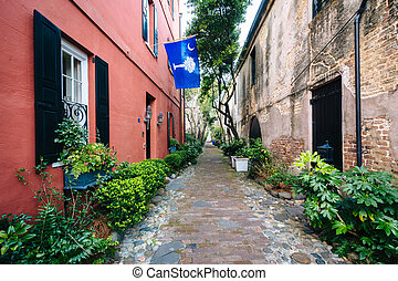 Narrow cobblestone street and old buildings in Charleston, ...