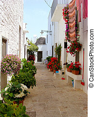 Narrow flower lined street in Alberobello, Italy with trulli house