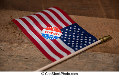 Narrow focus on I Voted Today paper sticker on US Flag