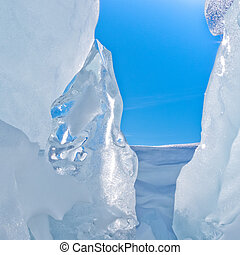 Narrow icy crevasse of glacier with some fresh snow and blue sunny sky visible in the opening