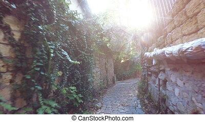 Narrow lane with sun in frame - Down narrow lane mountain...