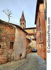Narrow paved street among houses in Saluzzo, Iyaly.