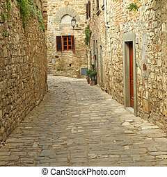 narrow paved street and stone walls in italian village, ...