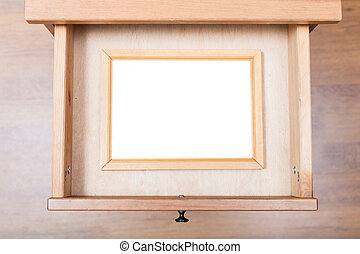 narrow picture frame in open drawer