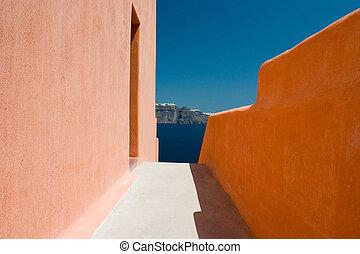 Narrow sidewalk between orange walls and island city afar off