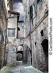 Narrow street between buildings (Siena. Tuscany, Italy)