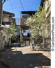 Narrow street, lane, tunnel with old houses, buildings on the sides in a poor area of the city, slums. Vertical photo