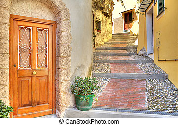 Narrow street. Town of Ventimiglia, Italy. - Wooden door at...