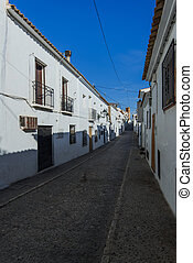 narrow street with white houses in Spain