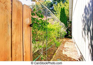 Narrow walkway behind the house leading to backyard area