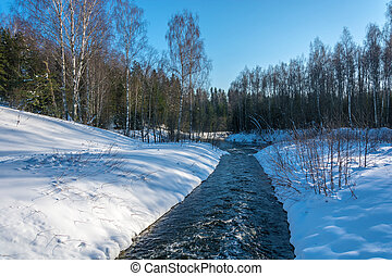 Narrow whitewater river in the snow banks.