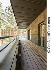 Narrow wooden terrace in modern house in the forest