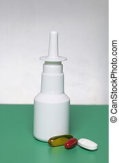 Nasal drops and spray stand on the surface. On a surface of green color, on a white background. Nearby lie medical pills of different colors.