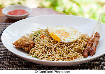 Nasi Goreng with fried egg, chicken Indonesian stir fried noodles Outdoor background