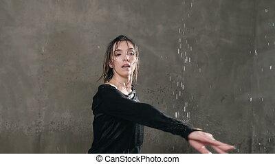 nasse, tänzer, tanzen, in, schwarze kleidung, und, kreise, ungefähr, selbst, unter, der, tropfen, von, wasser, in, der, studio., modern, dance., tanz, regen