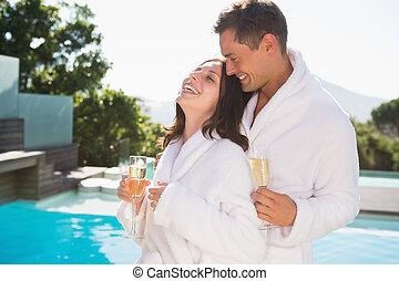 natación, pareja, alegre, piscina de champán, flautas