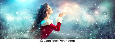 natal, scene., excitado, santa., morena, mulher jovem, em, partido, traje, soprando, neve, sobre, feriado, fundo borrado