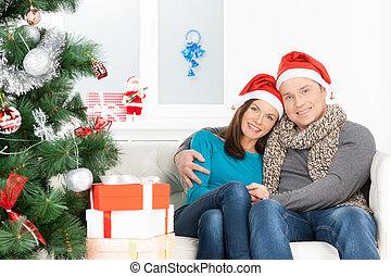 natale, eve., allegro, giovane coppia, in, cappello santa, seduta, chiudere, a, altro, e, sorridente