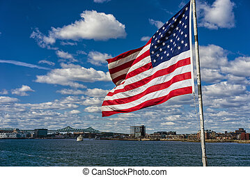 National American flag in front of city of Boston
