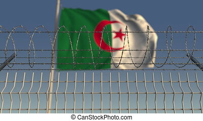 National flag of Algeria behind barbed wire fence....