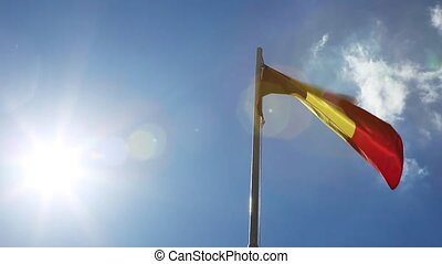 National flag of Belgium on a flagpole in front of blue sky