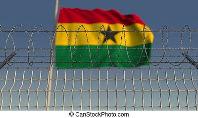 National flag of Ghana behind barbed wire fence. Conceptual...