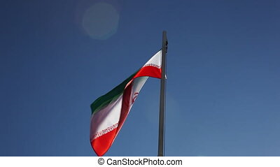 National flag of Iran on a flagpole in front of blue sky